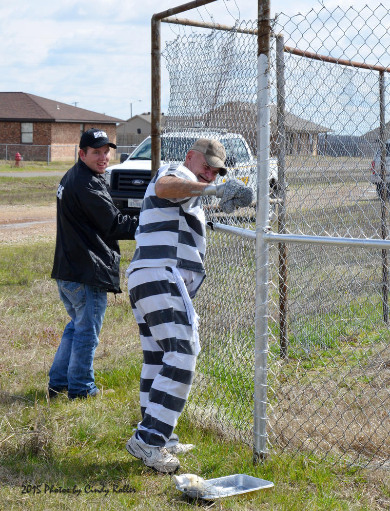Tanner Steward with the Delta County Sheriff's office oversees and assists with the painting of the youth ball park through the Inmate Work Program.