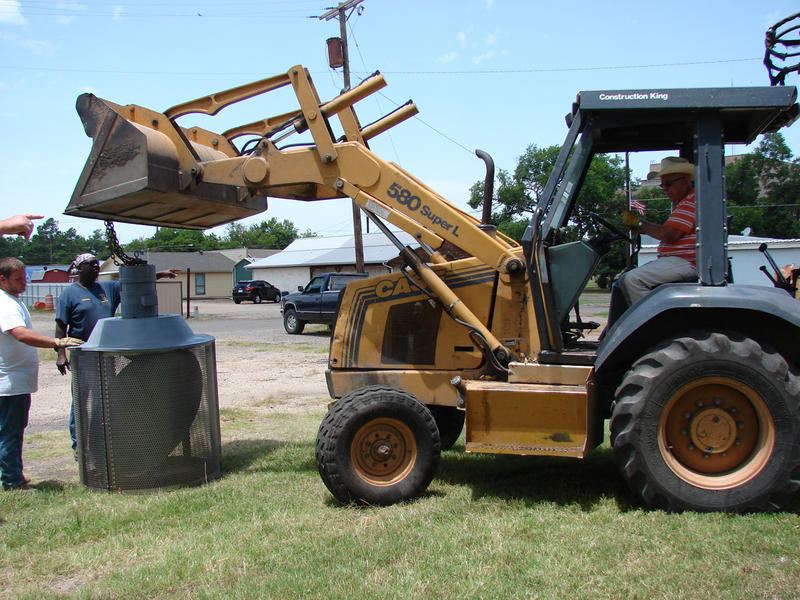 Mayor Scotty Stegall assists with a tractor to install the new reconditioned weather sirens.
