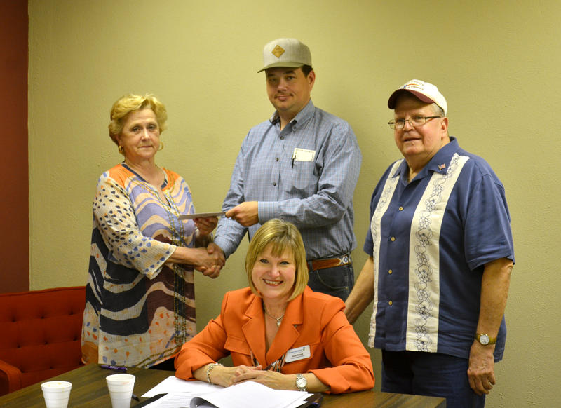 Delta County Economic Development members Sue Hommel (receiving check), Chairwoman Diane Stegall, and Dr. Torance Vandygriff accept $500 from Judd Murray on behalf of Delta County.