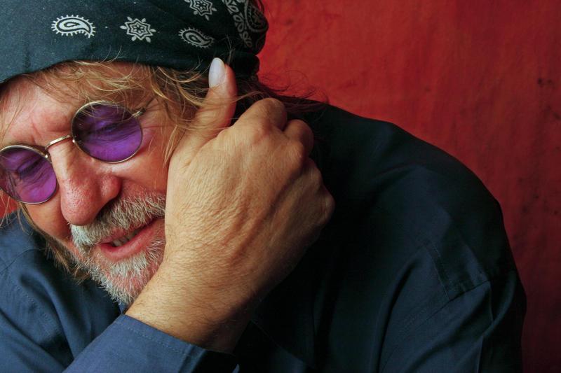 Ray Wylie Hubbard wearing blue bandanna, purple tinted sunglasses