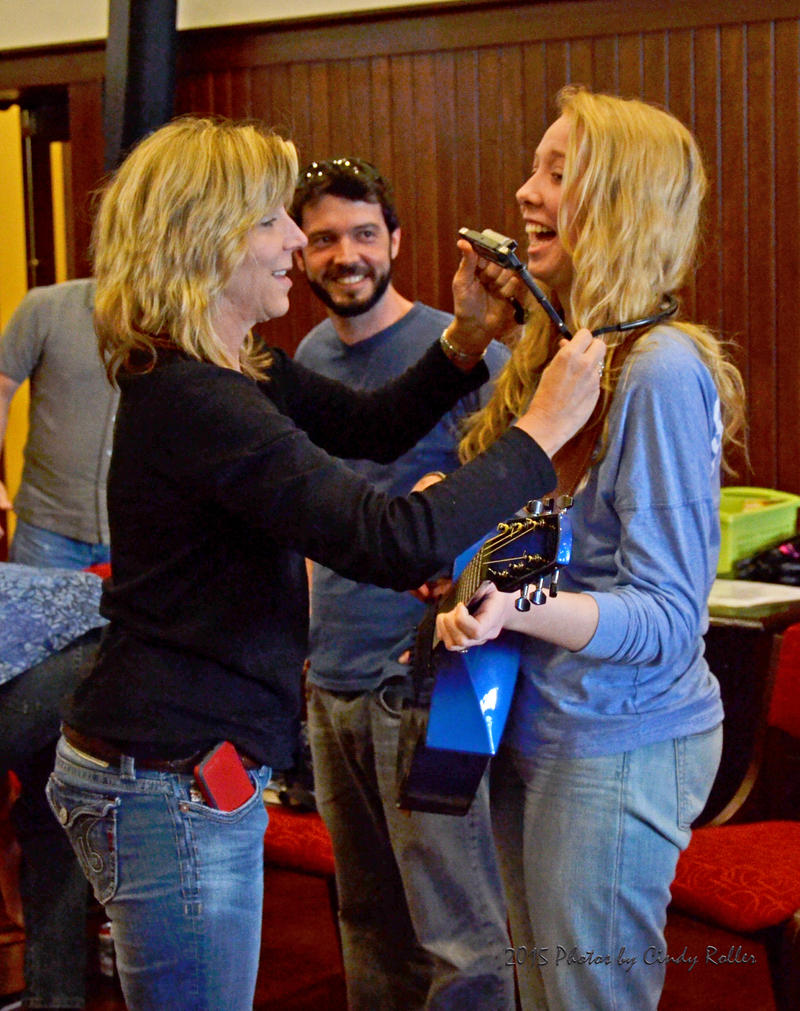 Grammy award winner Terri Hendrix outfits 16-year old Sadie Evans with a guitar and harmonica having fun during the very relaxed singer/songwriters workshop.