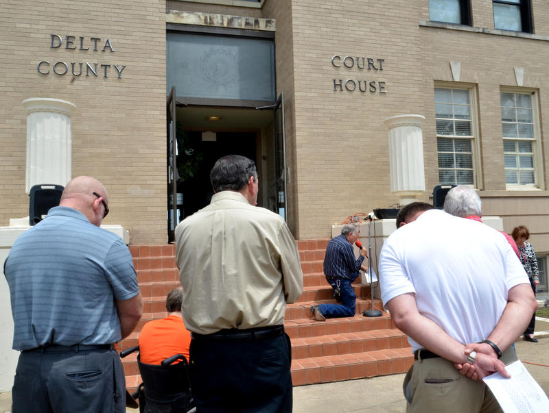 Citizens gather in prayer on the steps of the Delta County Courthouse.