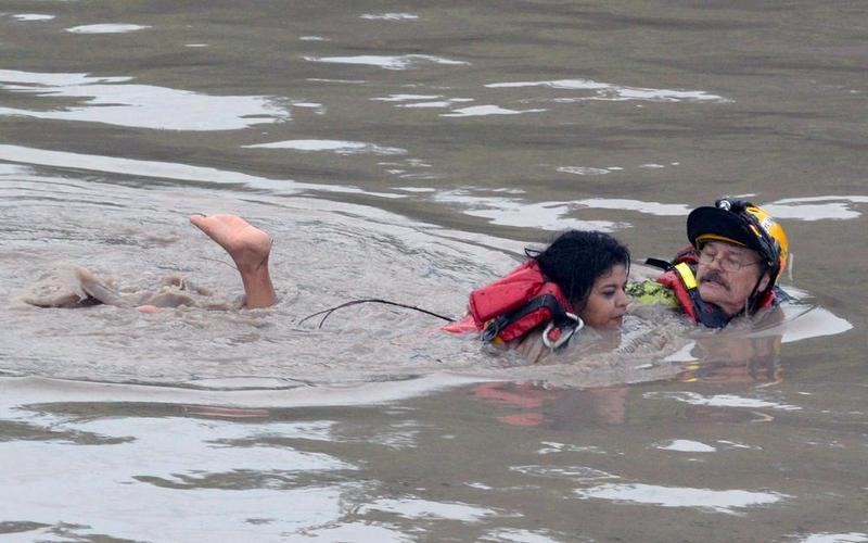 A San Marcos firefighter rescues a woman from floodwaters.