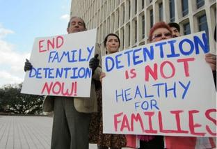 """Protesters hold signs reading """"End family detention now!"""" and """"Detention is not healthy for families."""""""