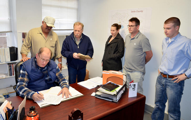 Delta County Emergency Management Coordinator Monty Hobbs (seated) signs paperwork with Commissioner Gary Anderson. Also present was Mark Brewer, Lindsay Kempner, Barron McLeod, and Tanner Crutcher.