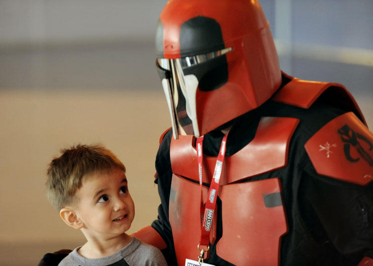 A young boy trying to peek under a red Mandalorian's helmet