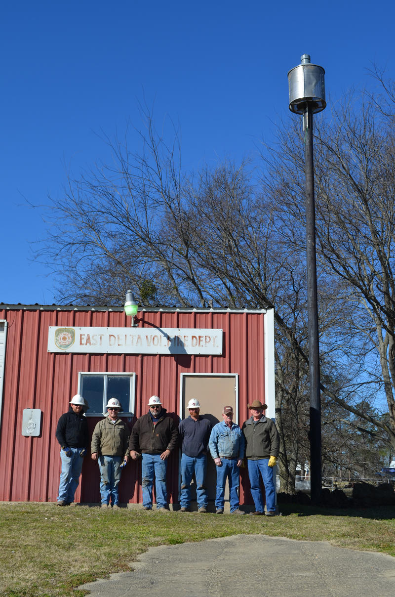 Lamar Electric employees David Roberts, Dustin Dale, Ronnie Bridges, Drew Conder and Jim Williams along with Delta County EMC Monty Hobbs stand next to newly installed storm warning siren.