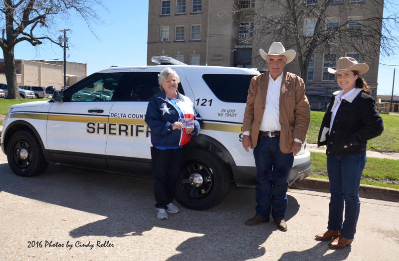 "Enloe United Methodist Church member Cheryl Cash presents the ""In God We Trust"" decals to the DCSO in behalf of the church to Sheriff Ricky Smith and Chief Deputy Charla Singleton."