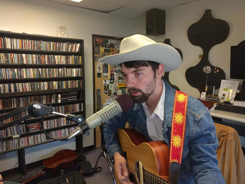 Christian Sparks playing guitar and singing during a live performance at Notably Texan Headquarters.