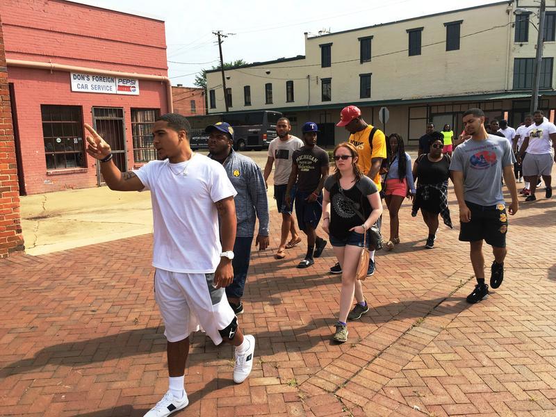 Students Richard Cooper, Chris Richardson, Devon Watson and others walk through downtown Selma, Ala.