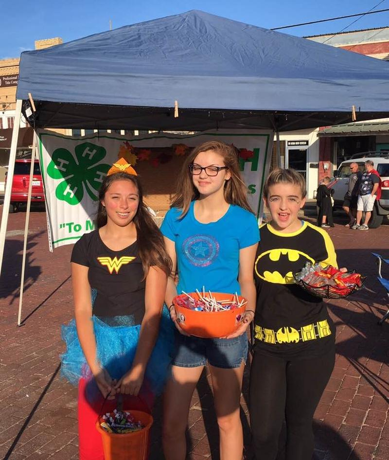 4-H officers Marissa Welch, Ann Marie Sokol, Lynlee Atchley helped give away candy on the Square in Cooper.