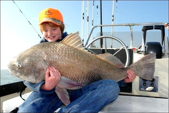 One of the fishermen and a big black drum he caught with Capt. Mike Williams' team