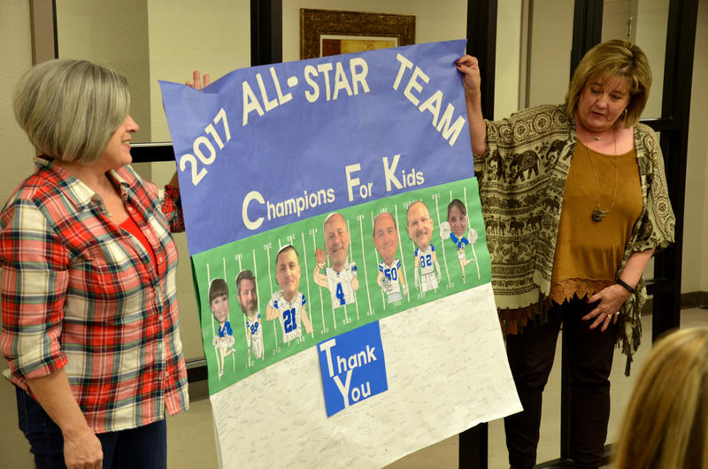 "Head Start Director Janet Walker and Cooper Elementary Principal Lynn Byrd display a ""Champions For Kids"" banner with the photos of the Cooper ISD School Board of Trustees as Dallas Cowboys football players in honor of School Board Appreciation Month."