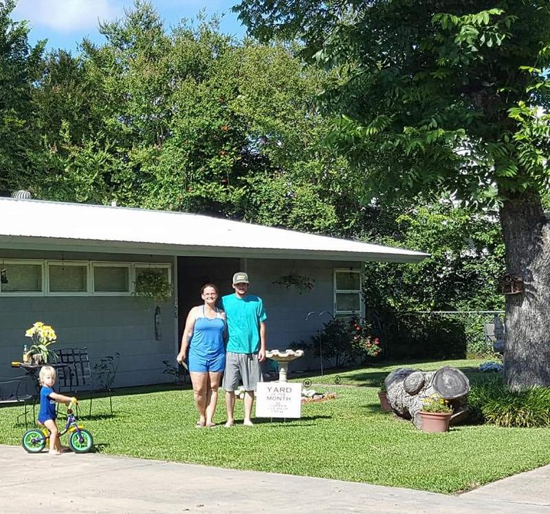 "Cooper Clean-Up Crew's first ""Yard of the Month"" winner is Misty Scott. She lives at 150 West Waco in Cooper. Pictured with her is Colton Wilson and on the bicycle is William Moore."