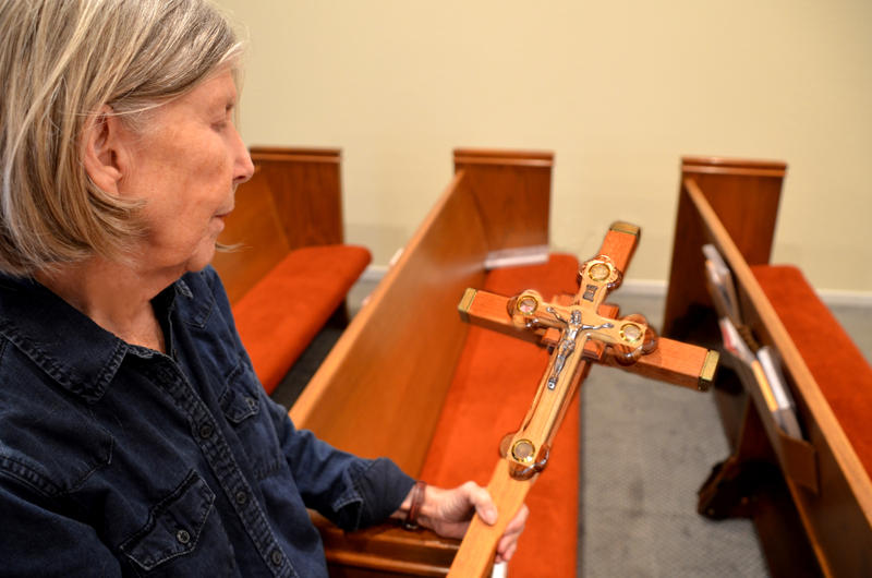 Lynne Morris reminsces about the blessing of the cross standing among the empty pews of St. Clare Catholic Church in Cooper, Texas.