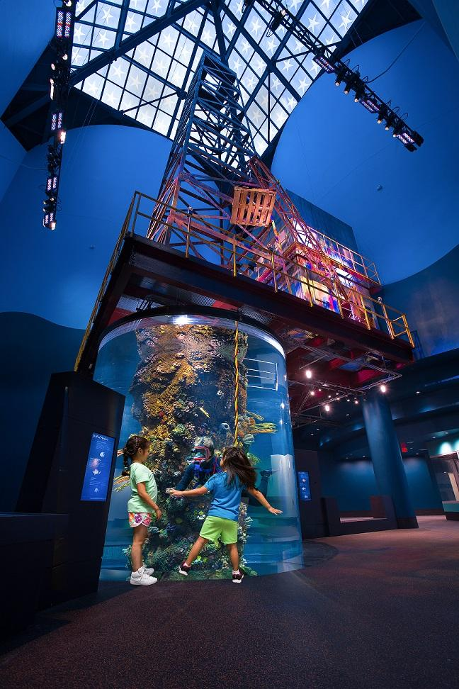 Visitors dance with an aquarium diver swimming inside an oil rig-turned-aquarium.