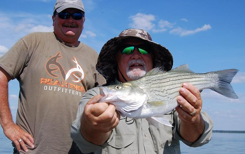 Cooper Lake guide Tony Parker and friend Deryl Markgraf show off a hybrid striper catch