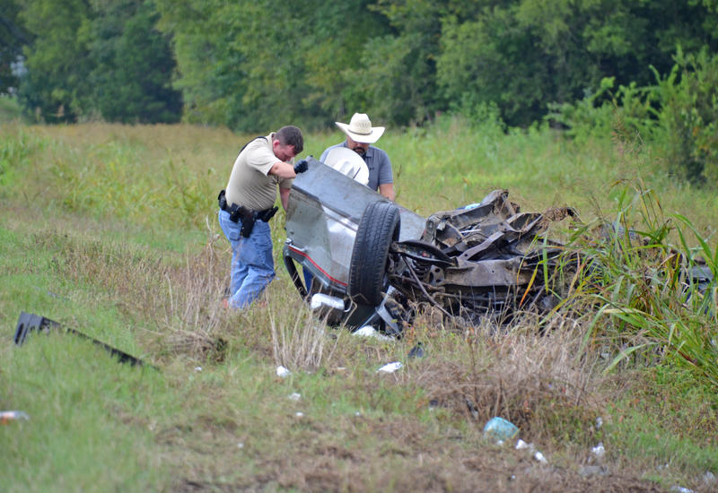 First at the scene Delta County Deputy Tanner Steward and Delta County Constable Marshall Lynch along with Deputy Elmo Robinson examine the wreckage of the Dodge pickup.