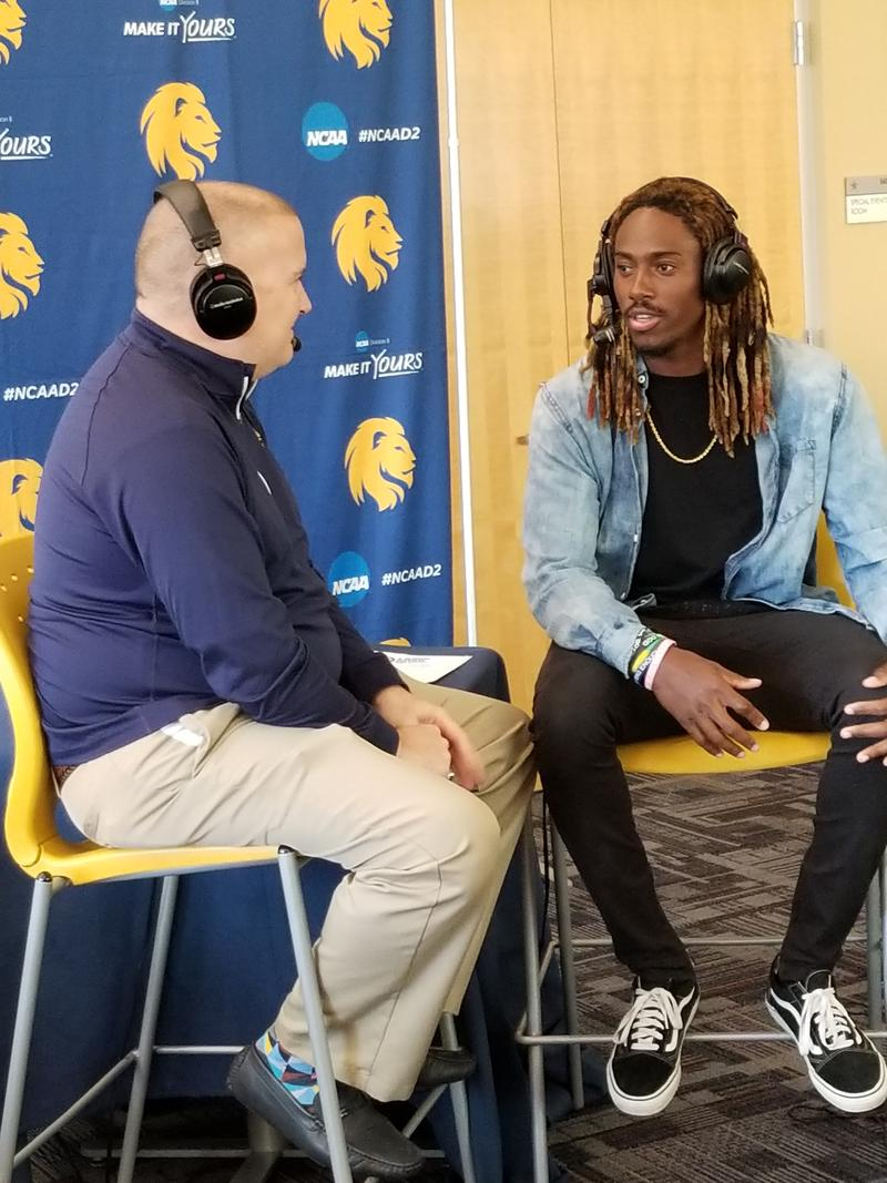 Tim McMurray also talks with junior defensive back Chris Smith of the Lions football team.