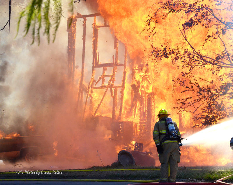 Cooper VFD struggles to fight back the flames of the two-story house fire.