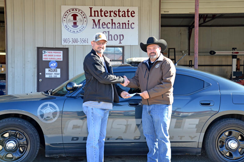 Interstate Mechanic Shop owner Chuck Sickles donates to Constable Marshall Lynch.