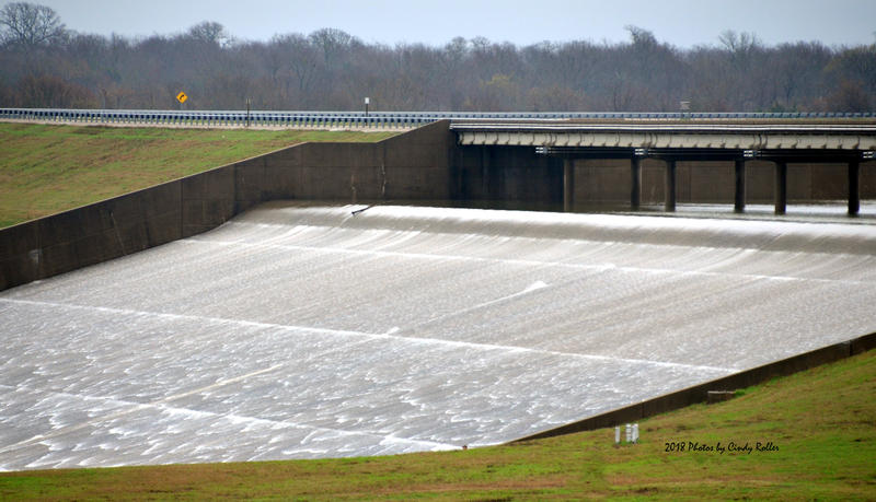 The uncontrolled spillway is releasing over 11,000 cubic feet of water per second.