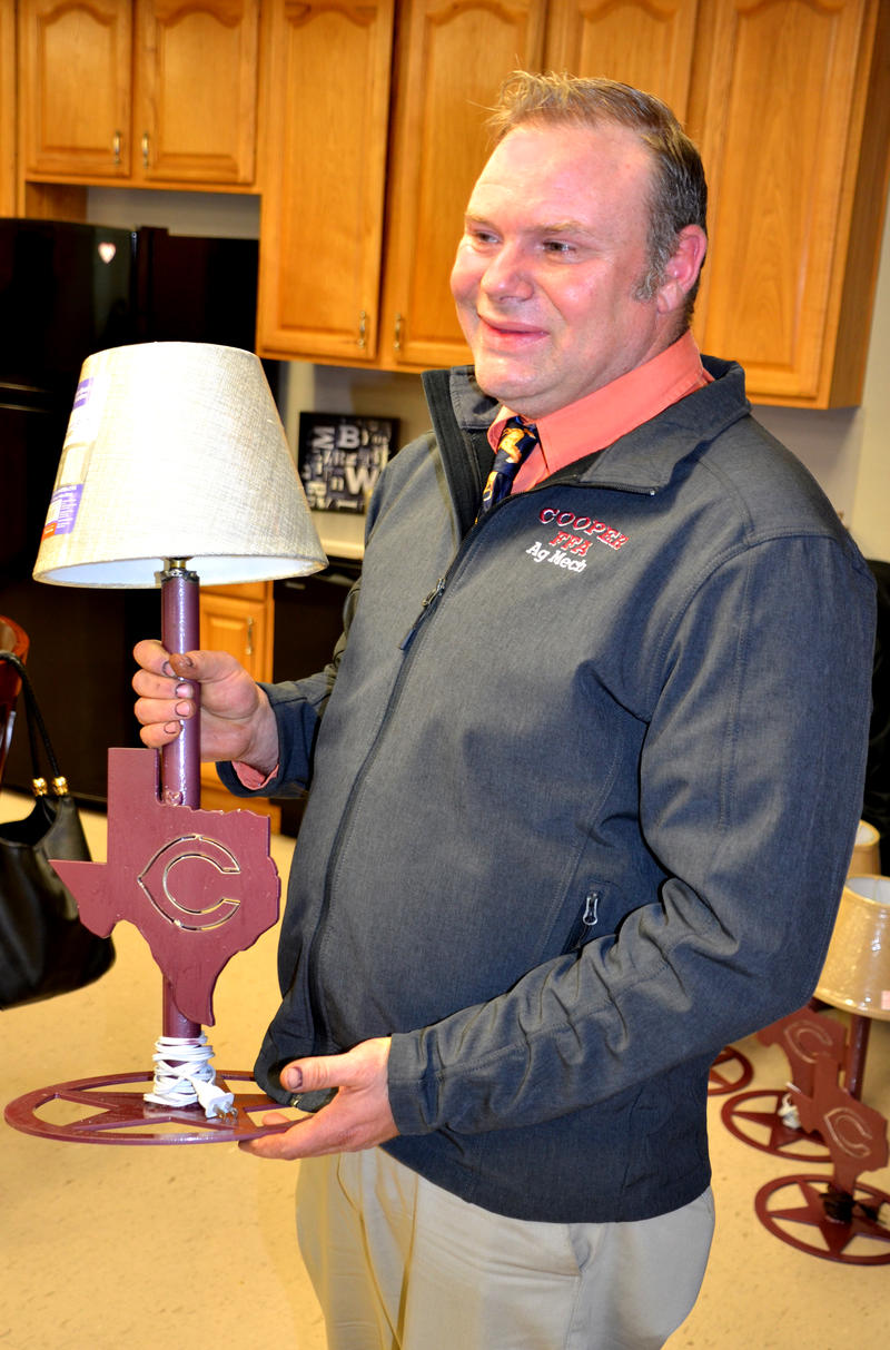Instructor Billy Fowler helps present crafted metal lamps to the Board.