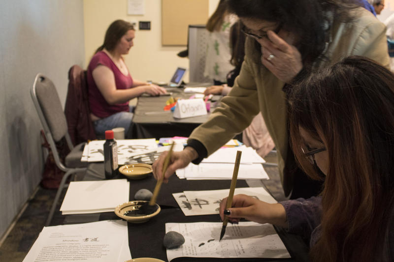 Students being taught Japanese caligraphy.