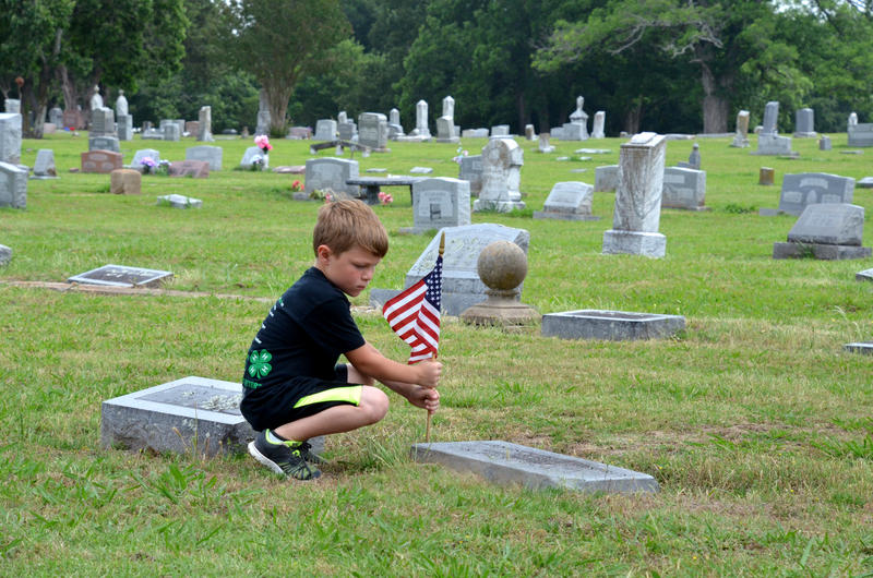 Adults and children volunteer to help place flags. Post 483 will be placing flags at 9 a.m. on Saturday, May 26.