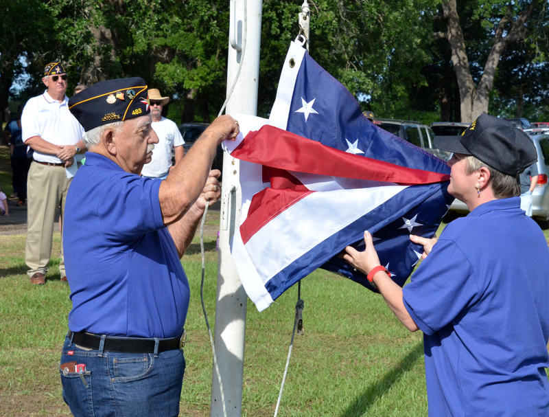 Post 483 EJ Cates and Diane Bosscher raise the flag over Oaklawn Cemetery.