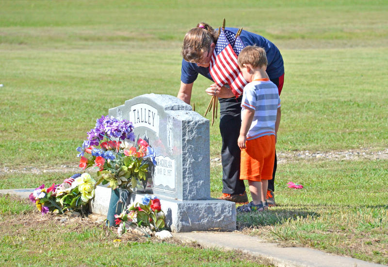 Tammi Springett and her grandson Landon Fouse place a flag on the headstone of LC Talley at Oaklawn Cemetery in Cooper for the Memorial Day holiday.