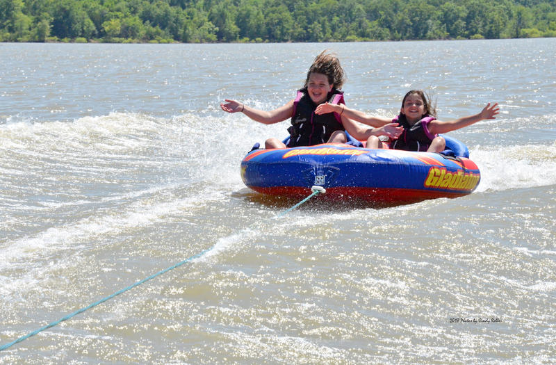 Summer has officially arrived as Sydney Mitchell and Maddie Poskey enjoy riding on a tube on Cooper Lake.
