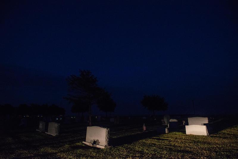 Headlights illuminate gravestones at a cemetery north of Terrell, TX.