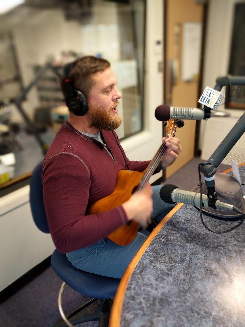 "Matthew Fiock playing the ukulele and singing his song ""Blaze"" in the KETR studios."