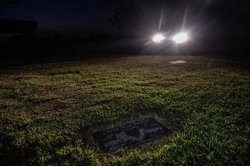 Headlights illuminate a headstone for Carey Mae Parker at a cemetery near Terrell, TX