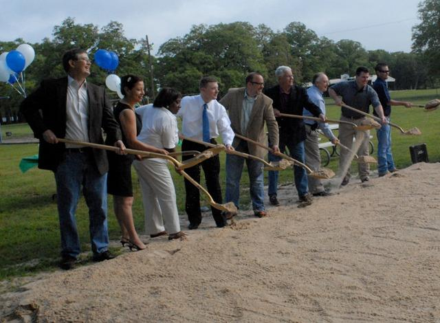 Greenville city officials and dignitaries toss dirt during Friday morning's ceremony