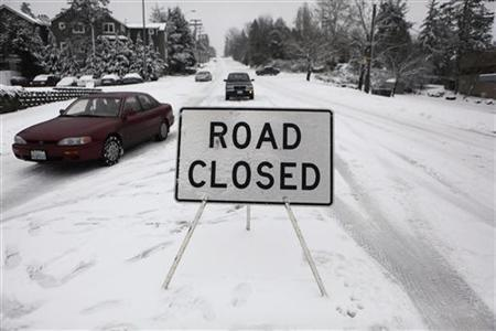 Vehicles ignore a road closure after a snowstorm moves through the area.