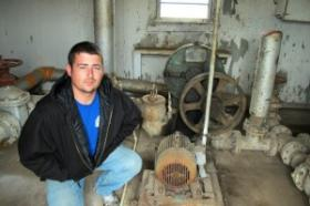 Justin Johnston crouching by sludge pump