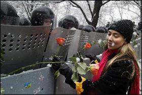 A protester in Kiev inserts roses into riot police shields on December 1, 2004.