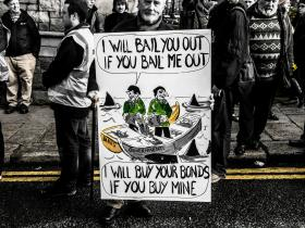 A demonstrator holds a sign protesting Ireland's continued bank debt - Feb. 9, 2013