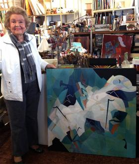 Artist Regina Murphy standing next to one of her works.