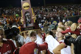 The Sooners gather around the National Championship trophy Tuesday night on the field of ASA Hall of Fame Stadium in Oklahoma City