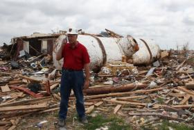 Tim Marshall, a meteorologist and civil engineer, stands near a water tank in a tornado-ravaged Moore neighborhood. The tank fell from the sky after being carried a half-mile, Marshall says.