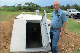 Wiley Robison shows off the new tornado shelter outside his home near Jay, Okla.