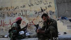 Free Syrian Army rebels clean their AK47s in Aleppo during the civil war - October 19, 2012.