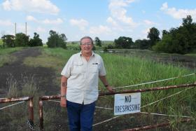Grand Riverkeeper Earl Hatley stands at the edge of the GRDA power plant's property near Chouteau, Okla