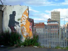 "The remains of a mural supporting the paramilitary Ulster Volunteer Force on a crumbling wall in Protestant South Belfast in 2007. It originally showed the UVF logo (a red hand surrounded by the words ""For God of Ulster"") flanked by two armed men."