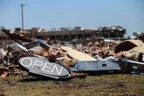 An open sign is one of the few items left after a tornado struck this convenient store in Moore, OK.