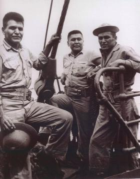 Pvt Floyd Saupitty (Comanche) pictured between two soldiers en route to Okinawa