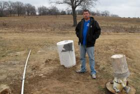 Justin Johnson, a wastewater treatment plant operator in Konawa, OK, stands near some of the town's water wells in December 2012.